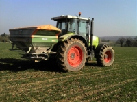 This is how we apply any fertilizer that the crop may require over the year. The tractor in the picture is a Class Ares 836, It is 4wd with about 215hp, It can lift about 9tonnes on the lifting arms at the back of the tractor.The spreader is an Amazon Zam twin disc spinner, This spreader can spread up to 36 meters wide.We have it set on 24 meters because this is the same width as our crop sprayer, That means we only need one set of wheel marks in the crop,Less damage to the crops. In this picture we are applying 150kgs/ha of 34.5% nitrogen (nitram)
